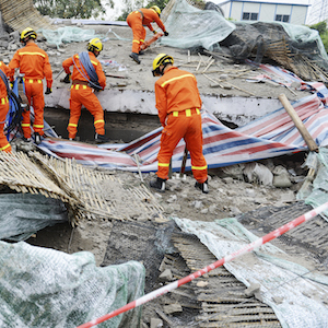 3.disaster relief workers orange suit on rubble