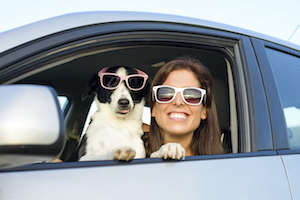 girl with dog in car both sunglasses